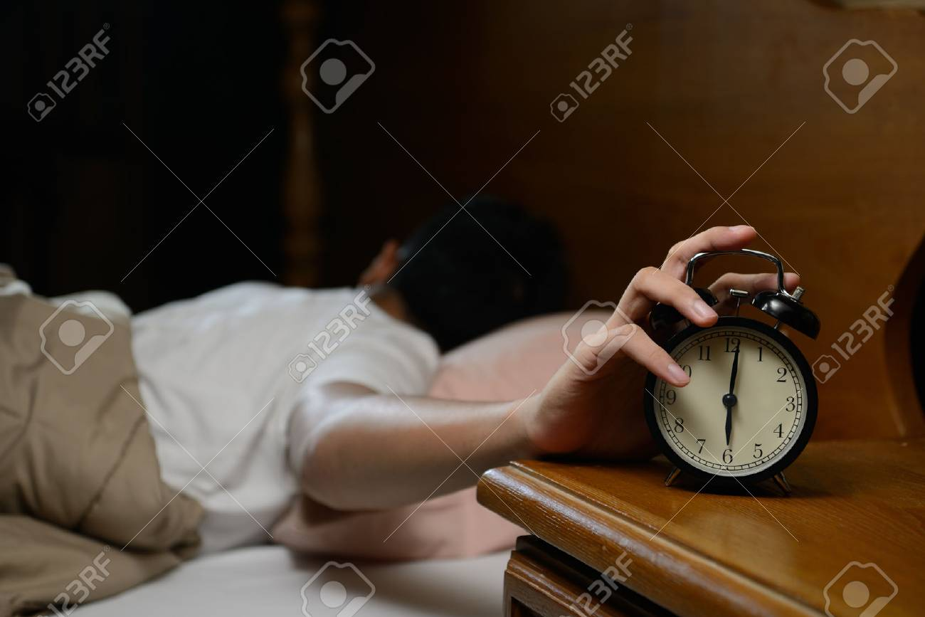 Young man turning off the alarm clock on the bed - 82975229