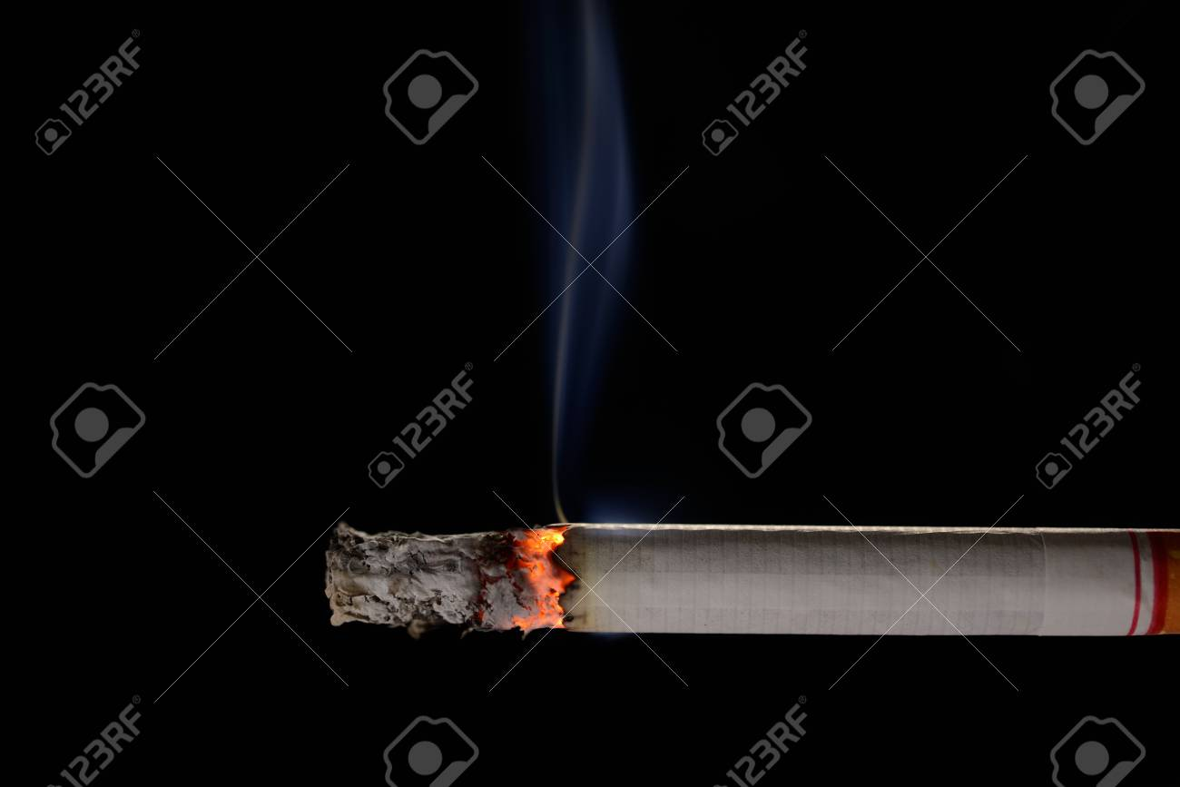 Lit and burning cigarette with smoke on black background - 82436251
