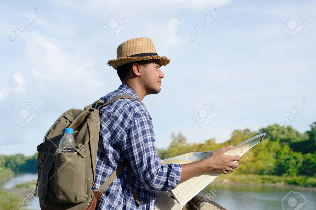 Young Asian tourist man with backpack and map looking at the nature - 90944400