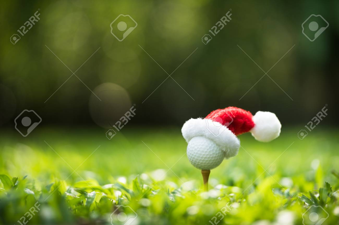 Festive-looking golf ball on tee with Santa Claus' hat on top for holiday season on golf couse backgroubd - 112411360
