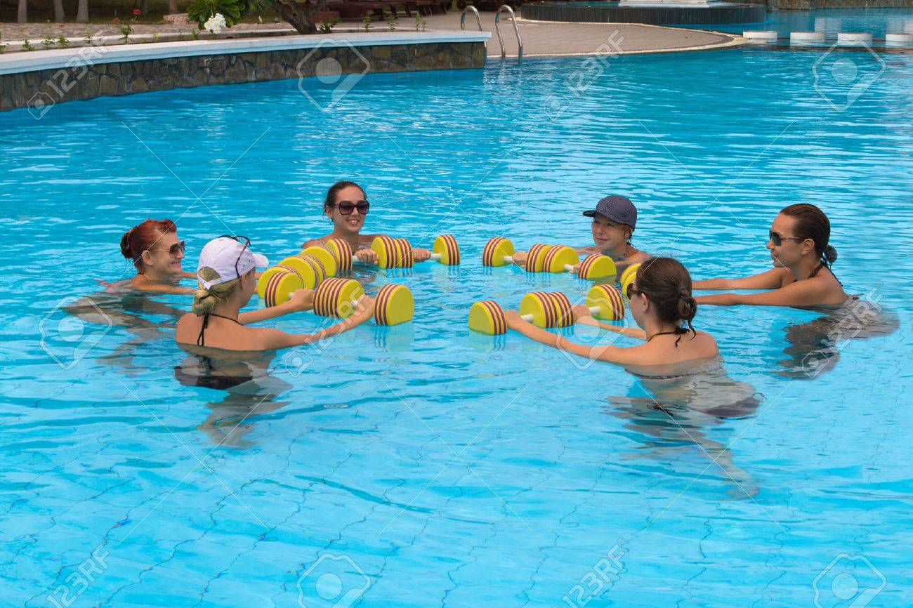 Aqua aerobic. Happy active fitness people doing exercise with..
