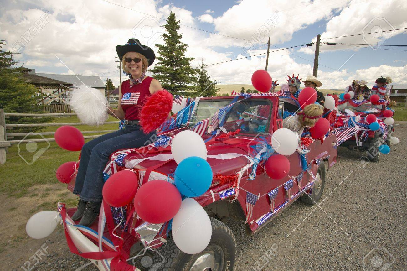 Woman sitting on the hood of a jeep decorated for the Fourth of July, in Lima Montana Stock Photo - 19962366