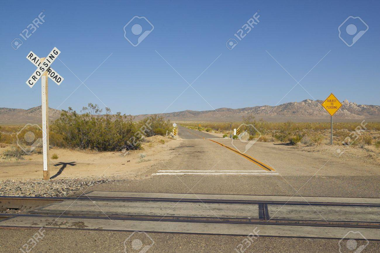 Railroad crossing sign and intersection in Mojave Desert of Southern