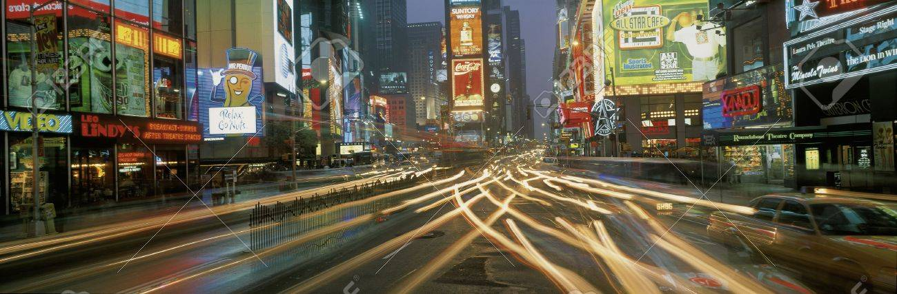 This is Times Square at night. There are streaked lights from the cars traveling through the square. There are neon lights from the billboards as well as signs. Stock Photo - 20515123