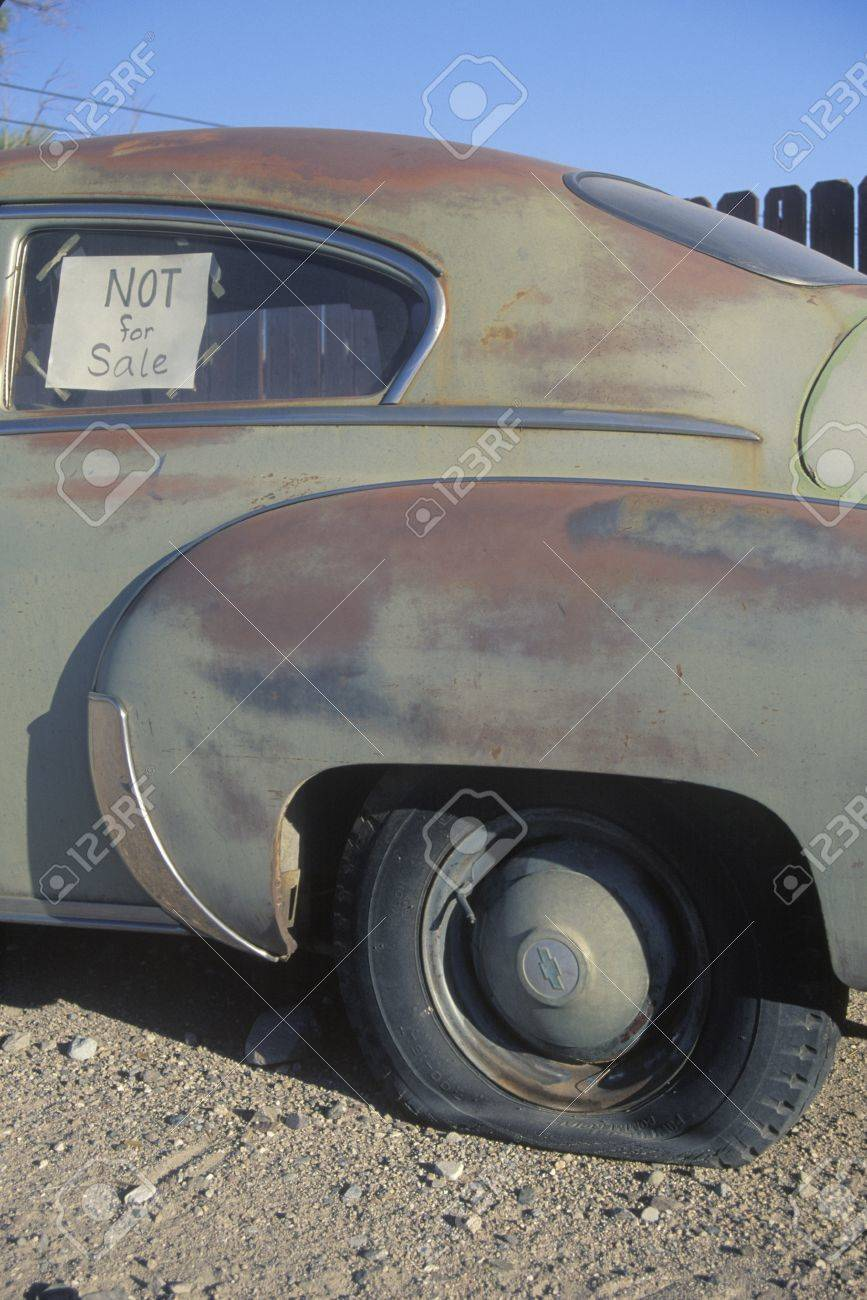 An Old Car With A Flat Tire Has A Not For Sale Sign In Its Window ...