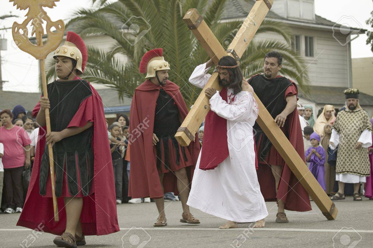 an actor portraying jesus christ carrying a cross past crowds