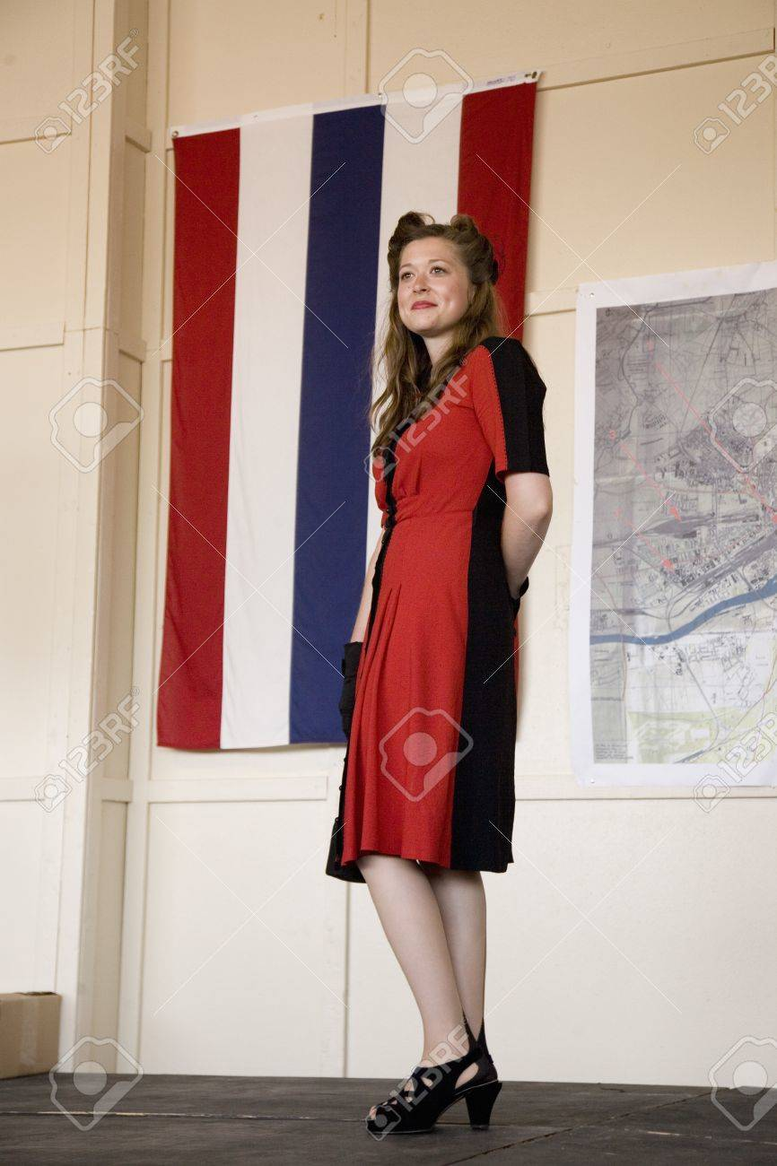Attractive woman in 1940s clothing posing in front of flag during