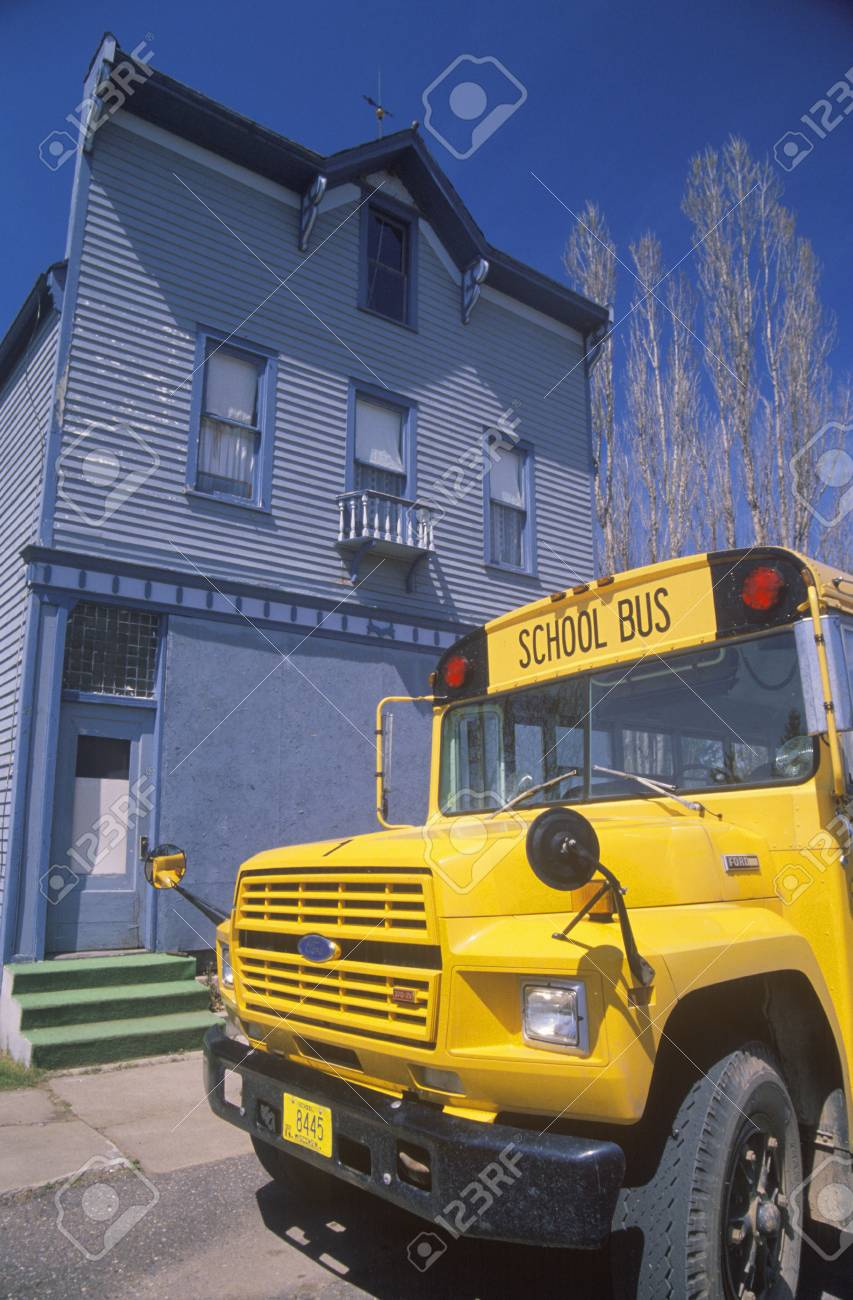 A Yellow Schoolbus Outside Of A Wooden Frame Building Port Wing