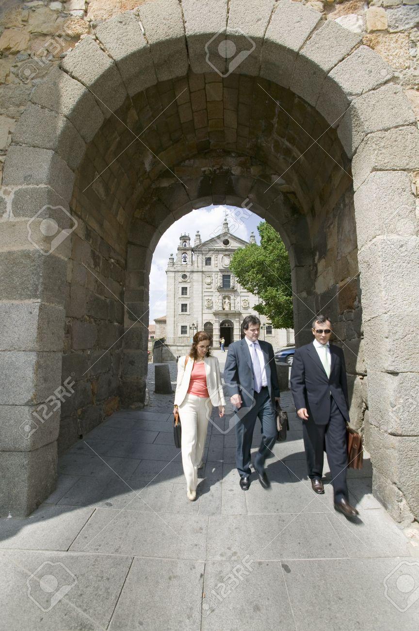 Three business people walk through gate of walled city, Avila Spain, an old Castilian Spanish village Stock Photo - 20766046