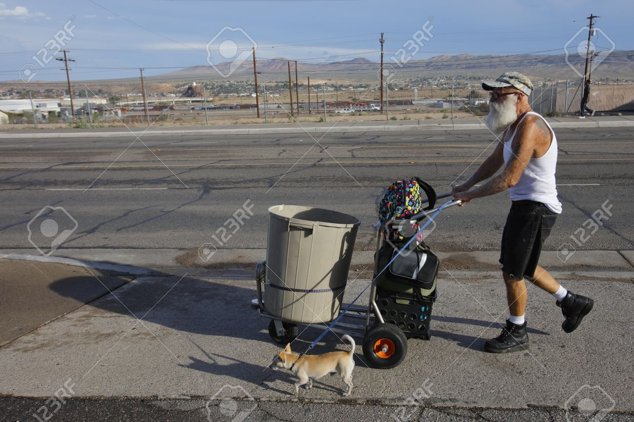 barstow ca homeless man in t shirt and dog pushes a shopping