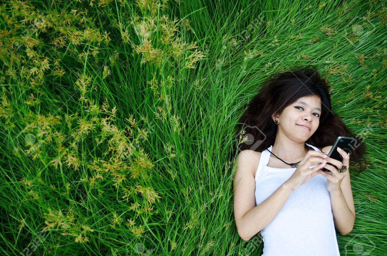 asian cute girl texting on meadow with happy face Stock Photo - 13408066