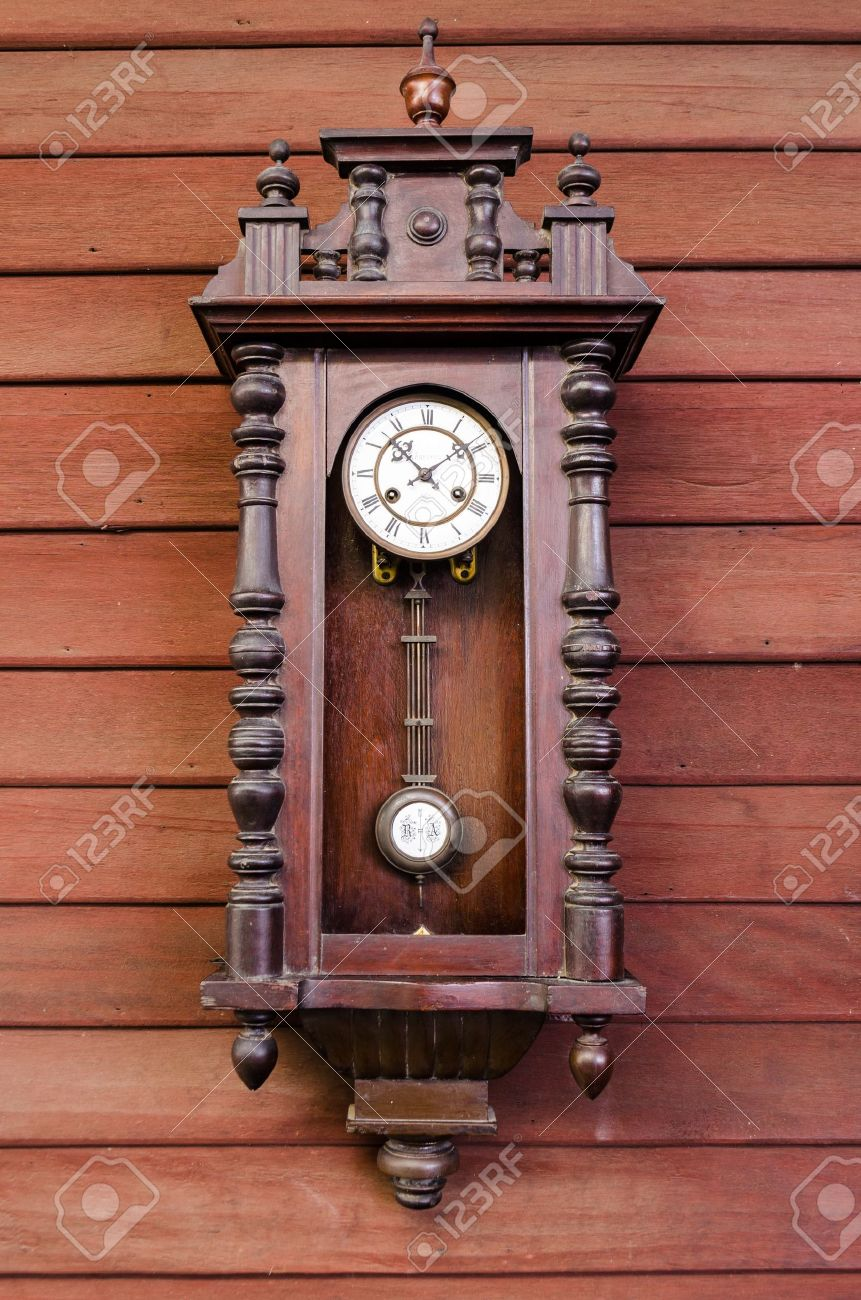 Antique Wooden Pendulum Clock Hanging On Wooden Wall Stock Photo