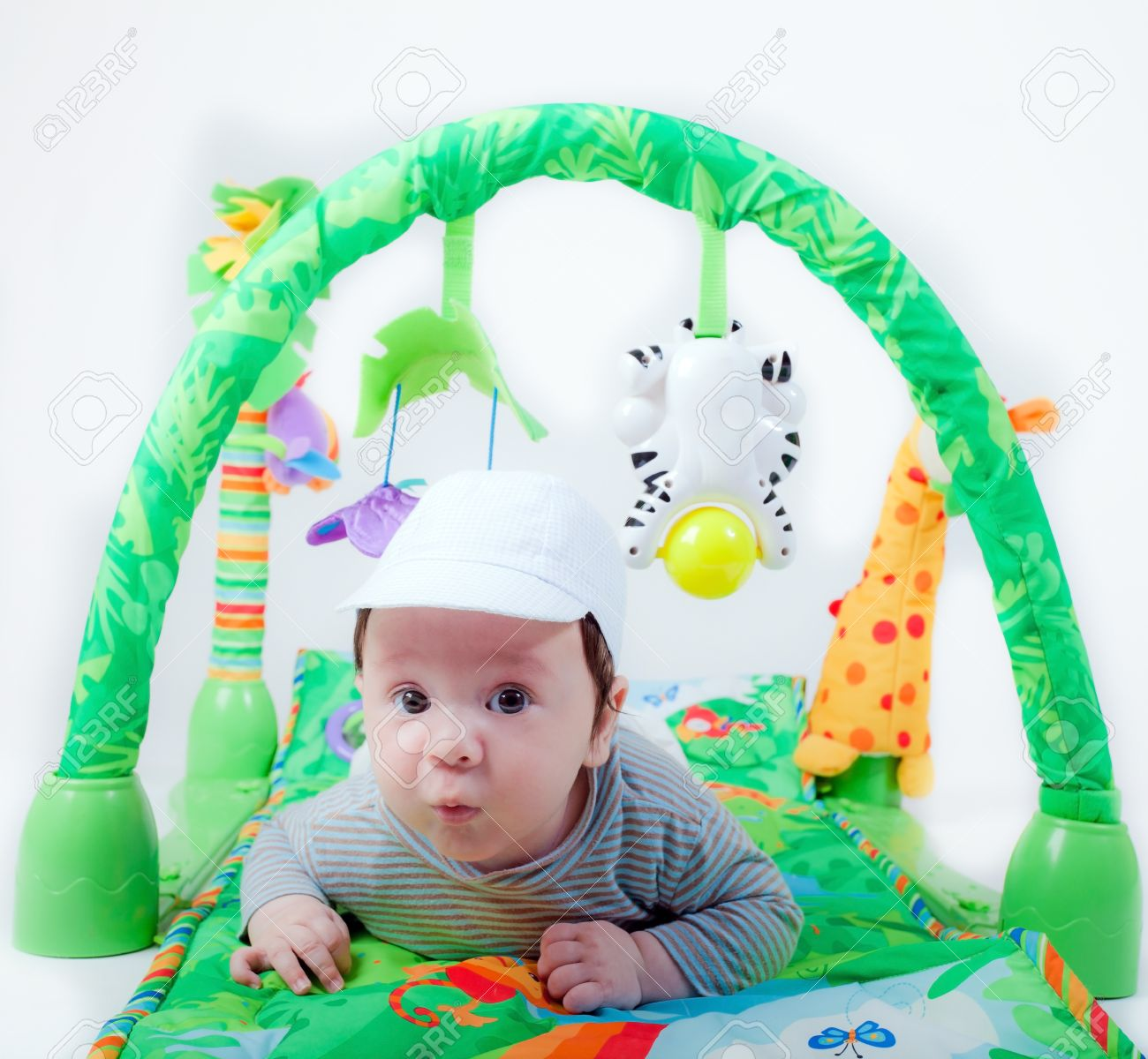 Sweet Baby Boy Is Lying Down On A Green Carpet Of Toys Stock Photo