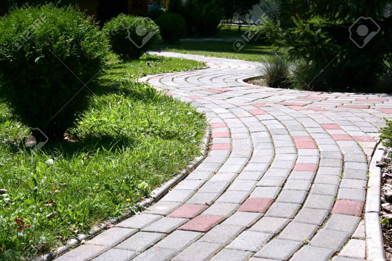 A stone walkway winding its way through a tranquil garden. Stock Photo - 15344830