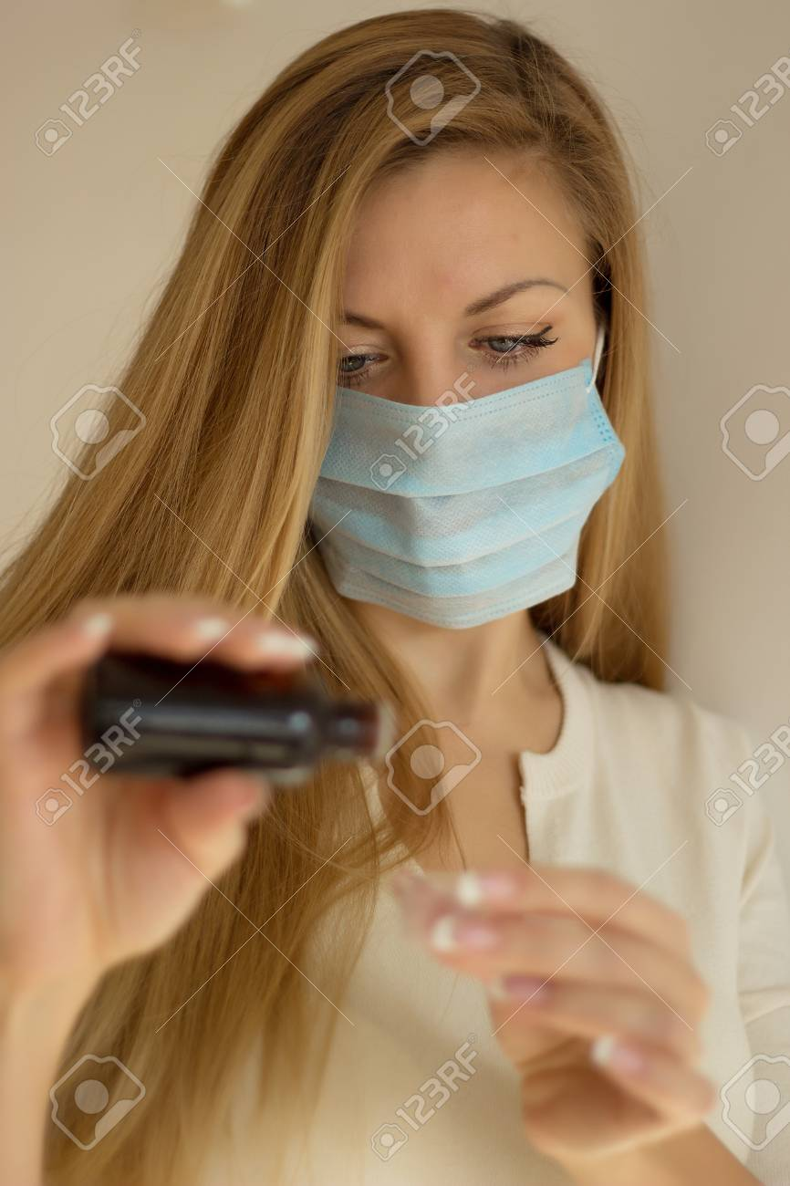Woman in mask hand holding medicine health care syrup. Shallow depth of field. Stock Photo - 18261875