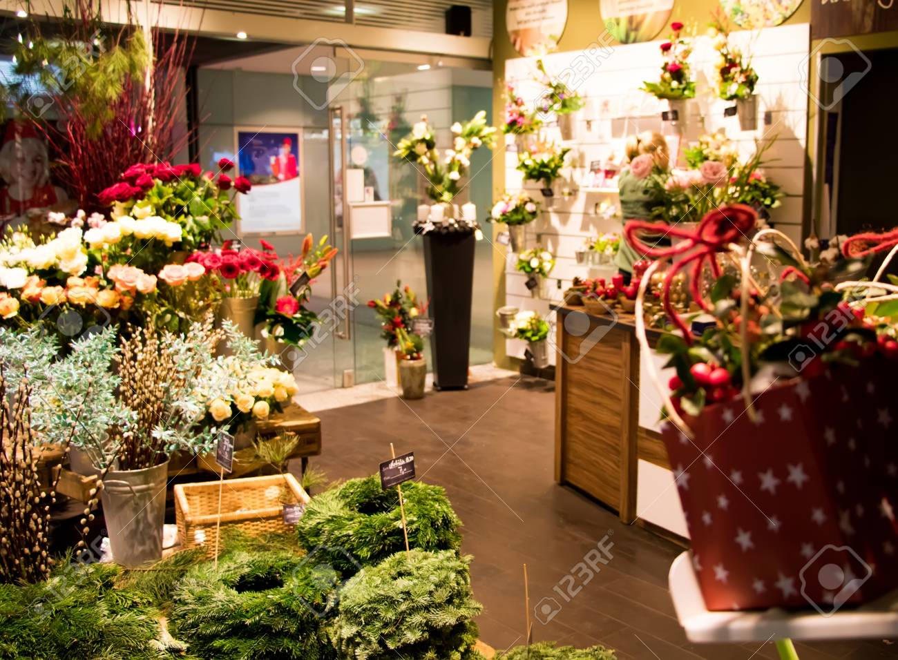 Small Florist Shop Selling Christmas Decoration, Fir Wreaths, Presents And  Flowers. Florist Workplace