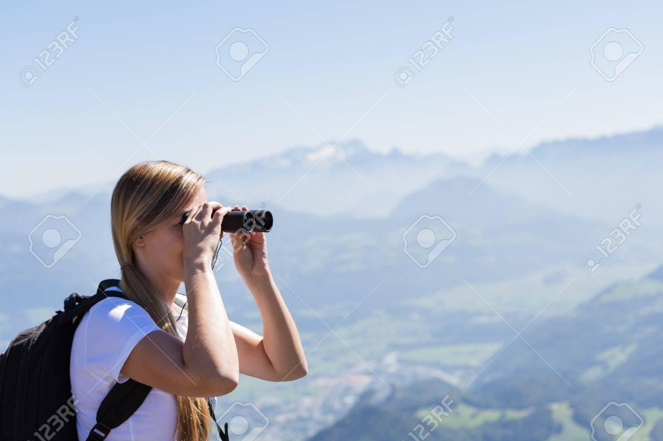 Junge frau mit fernglas auf einem berg während einer wanderung mit