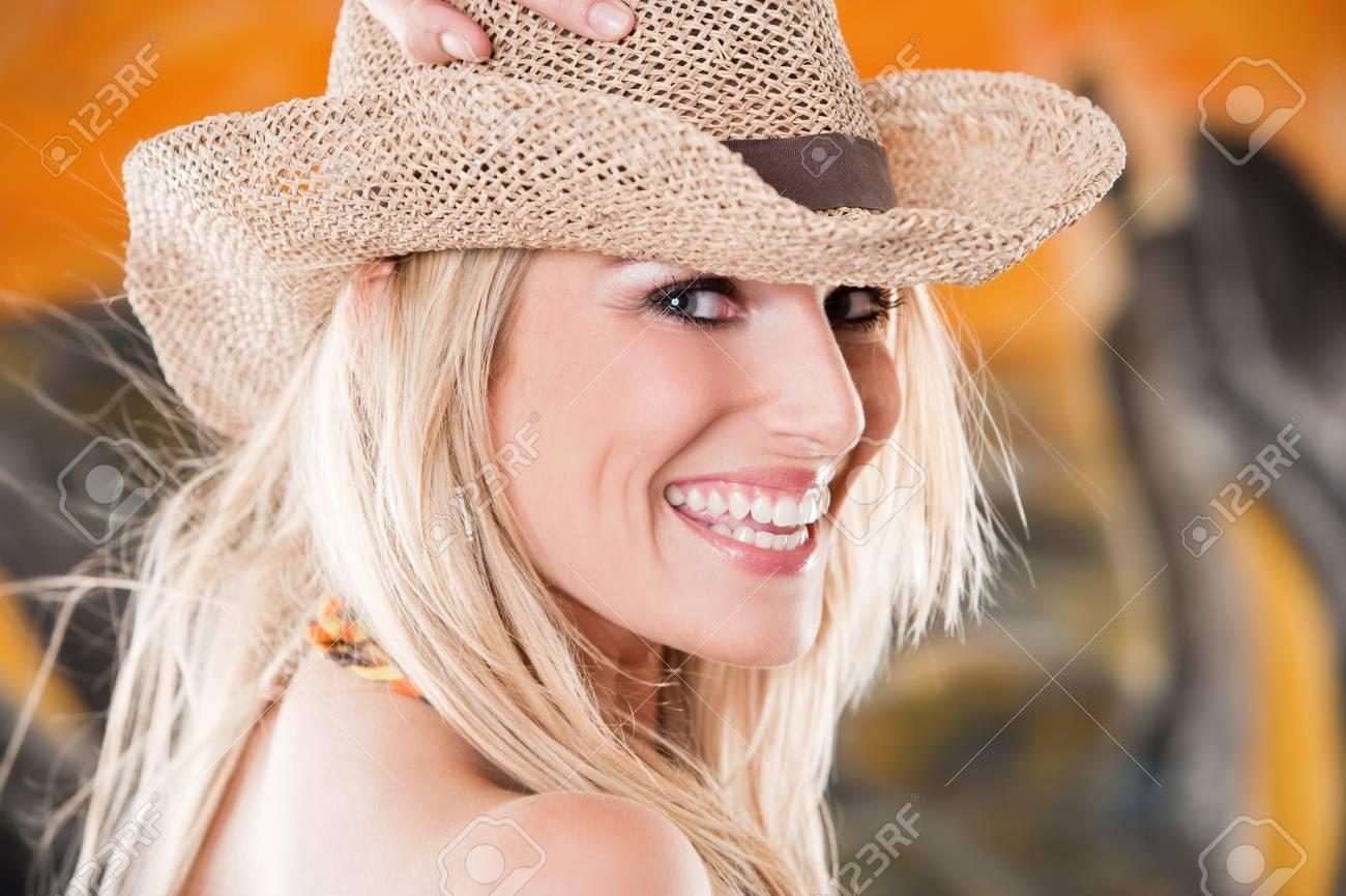 qualité-supérieure avant-garde de l'époque Braderie Rire femme vive dans un chapeau de paille avec de longs cheveux blonds  ébouriffés tenant la main à sa tête et se tournant pour regarder là caméra  avec ...
