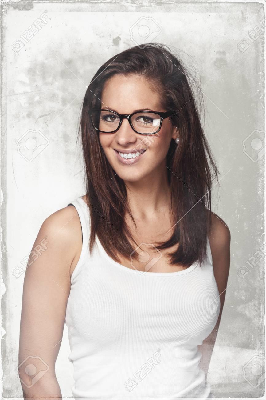 sélection premium vraie qualité toujours populaire Attractive jeune femme brune en lunettes tendance debout dans un t-shirt  d'été en regardant la caméra avec un sourire amical