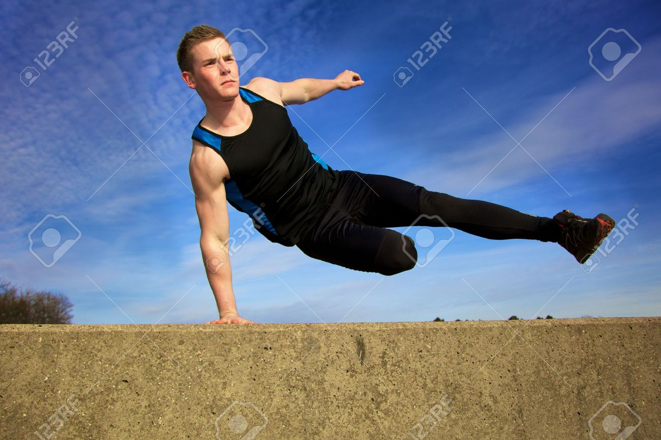 Young man jumping over wall on obstacle course Stock Photo - 9817343