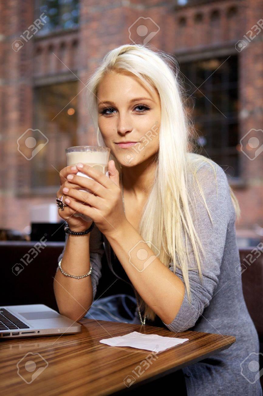 da74d6b3ec0c Archivio Fotografico - Ragazza sorridente seduto su bar con una tazza di  caffè.