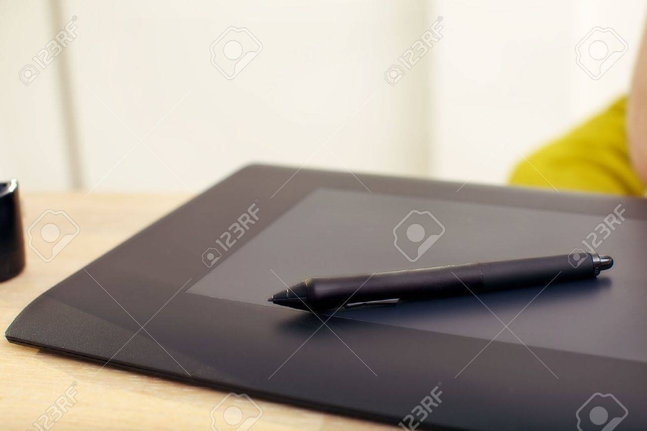 Clsoeup of a graphics tablet and pen on a desk. Stock Photo - 12248216