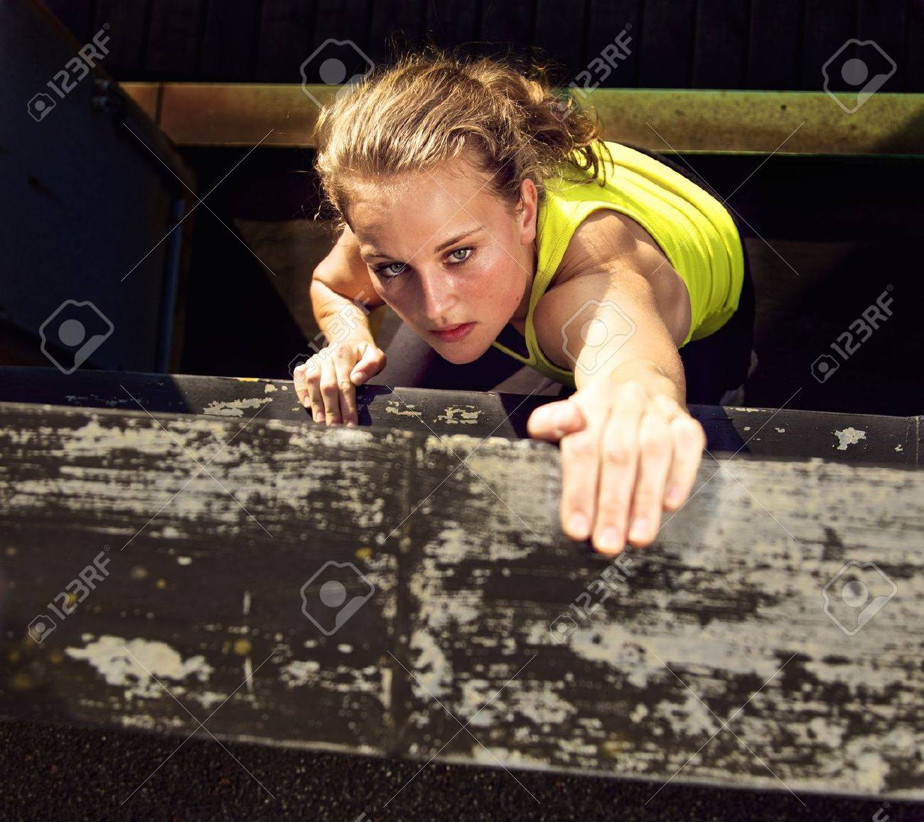 Determination on the face of a traceur climbing the wall of a high industrial building while demonstrating parkour Stock Photo - 12268537