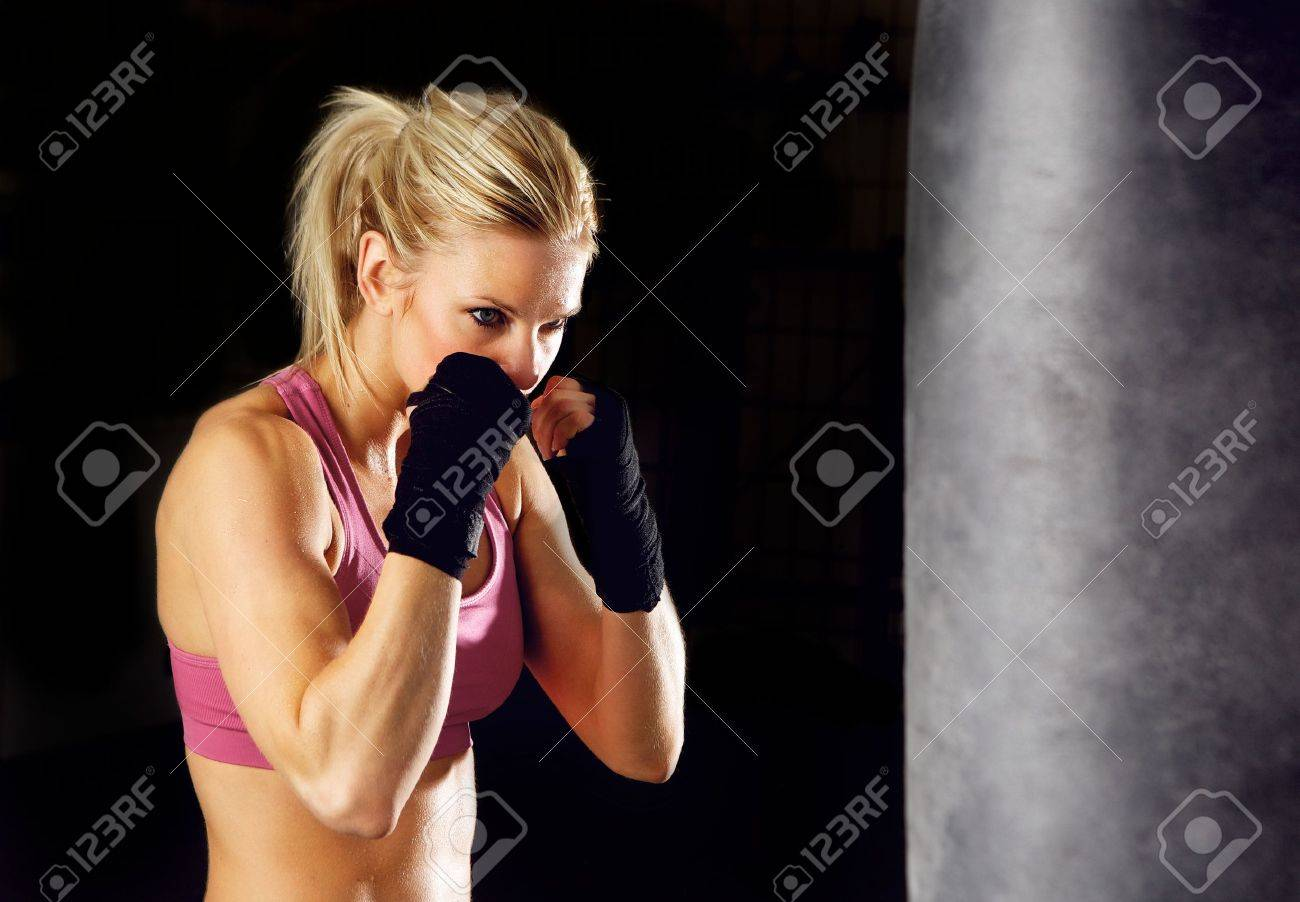 Young woman fitness boxing in front of punching bag  Isolated on black Stock Photo - 12883480