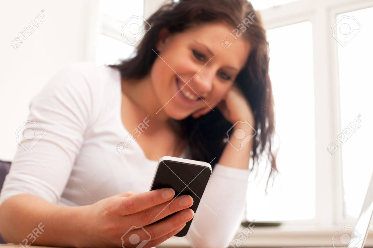 Portrait of a woman smiling while reading a message from her phone Stock Photo - 13296204