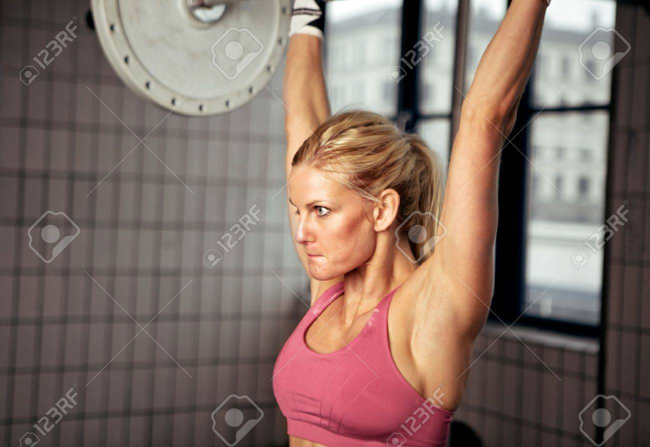 Fitness woman concentrating on lifting heavy weight in gym Stock Photo - 14157959