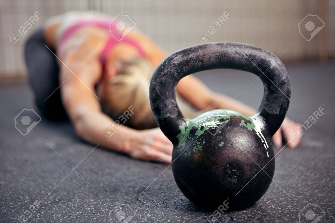 Young woman stretching her back after a heavy kettlebell workout in a gym - 14158006