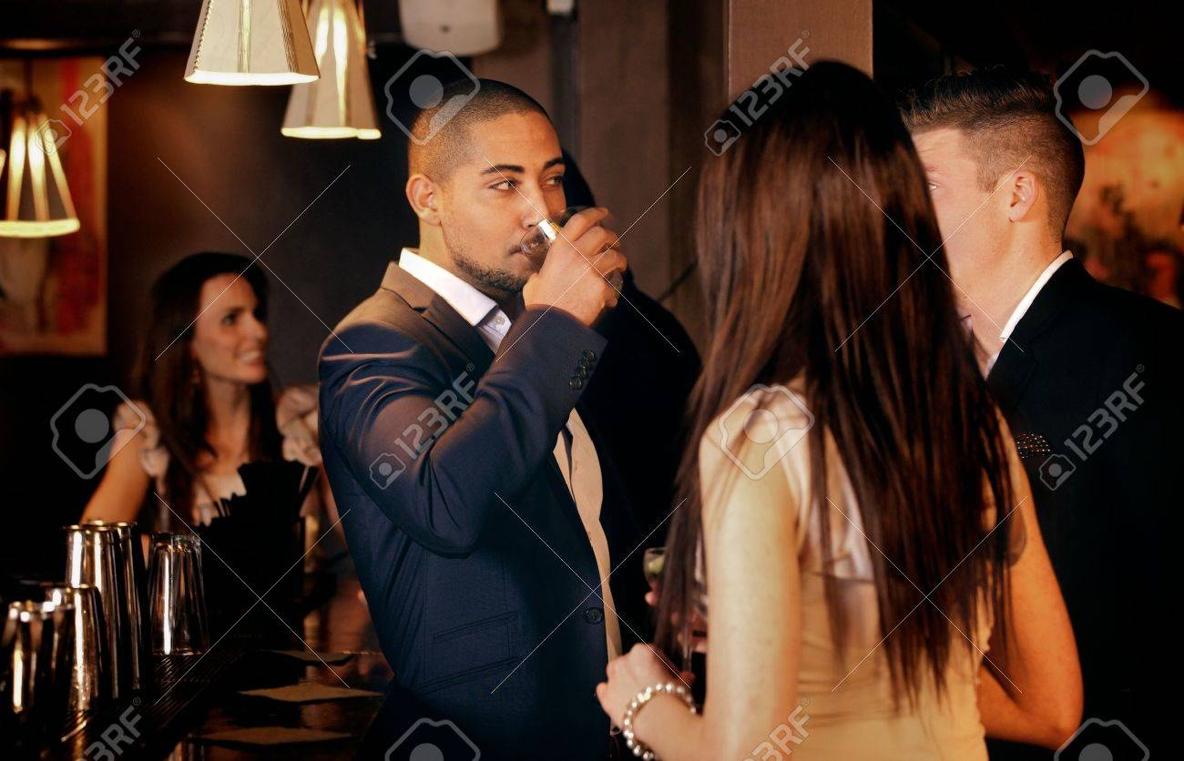 Group of friends standing while having conversation at a bar Stock Photo - 18635572