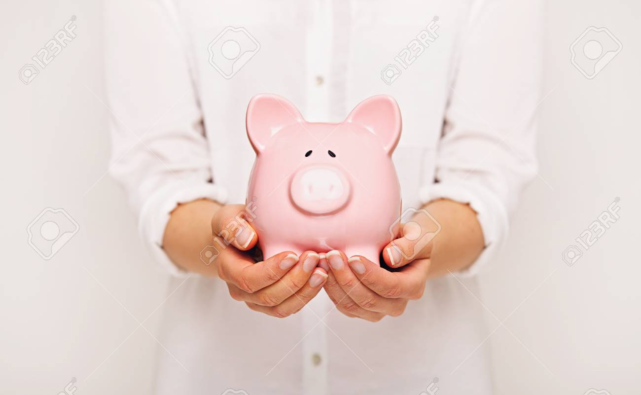 Woman holding a piggy bank with both hands Stock Photo - 21507300