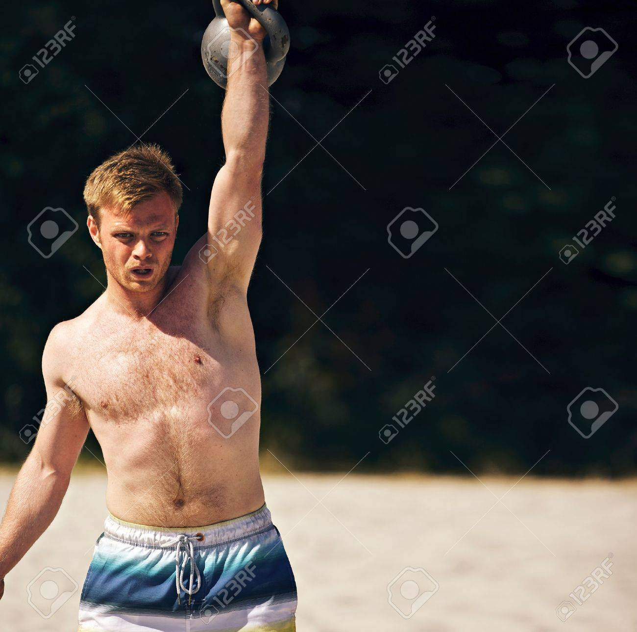 guy lifting a heavy kettlebell on a beach during crossfit workout