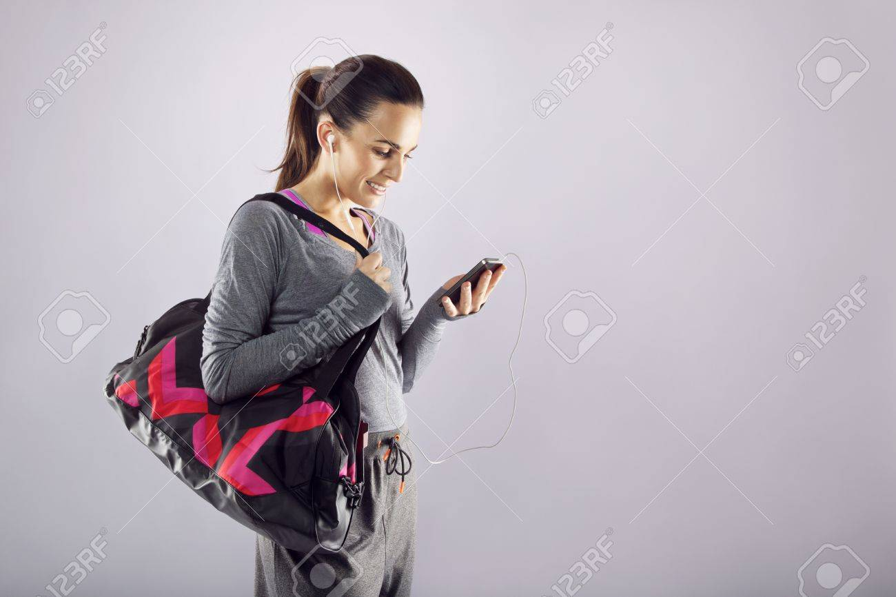 Good looking female athlete with a sports bag listening to music on her mobile phone. Fitness woman in sports clothing going to gym on grey Stock Photo - 23441662