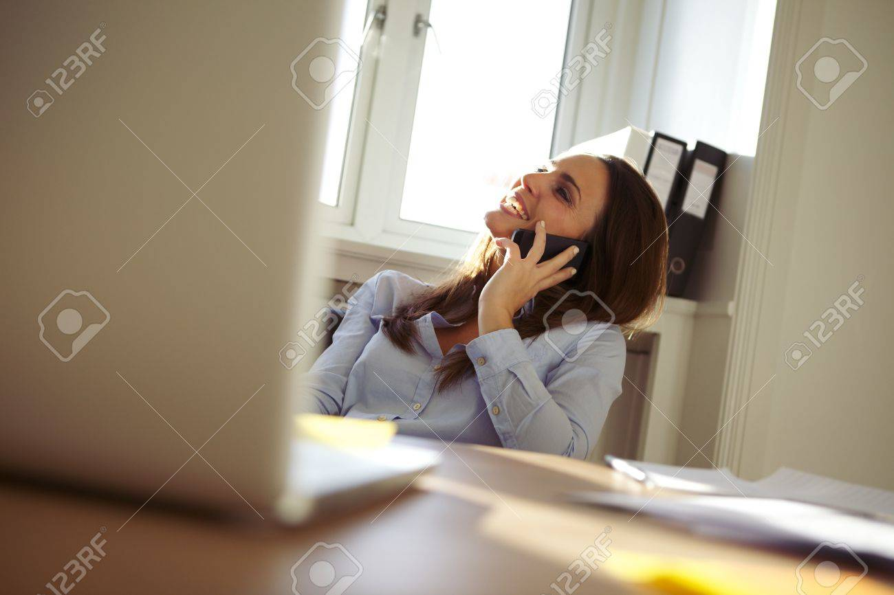 Beautiful young businesswoman sitting at her desk talking on mobile phone smiling. Pretty caucasian woman working in home office. Stock Photo - 24177946