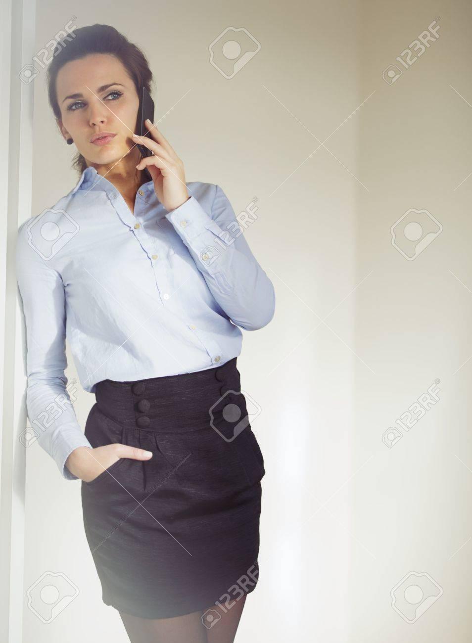 6bcf87058 Empresaria elegante vestida con falda y camisa hablando de negocios en el  teléfono. Mujer de raza blanca en los años 20 con el teléfono inteligente  ...