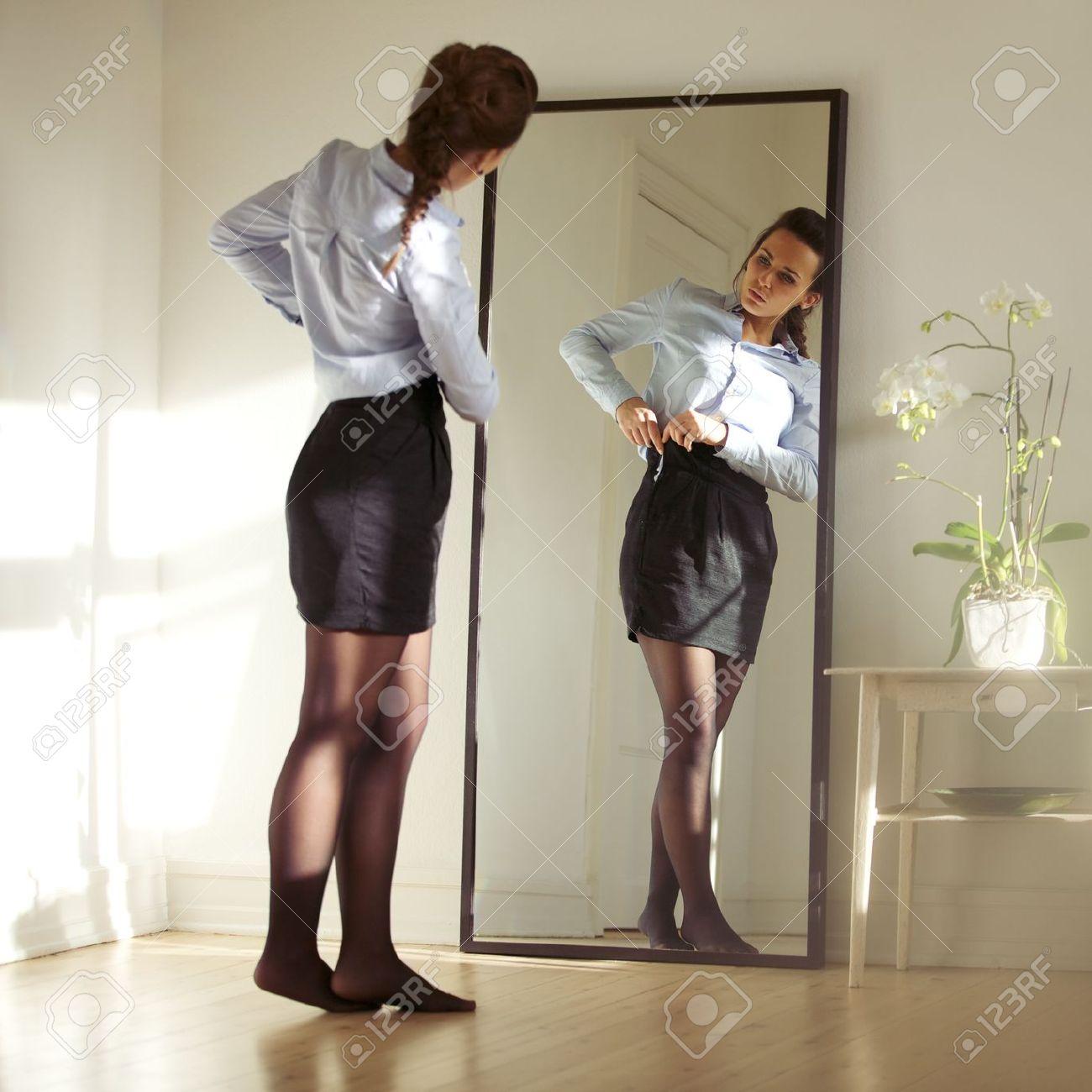 3846f33e6 Empresaria bastante joven que se fija la falda delante del espejo. Hermosa  modelo de mujer caucásica preparándose para el trabajo.