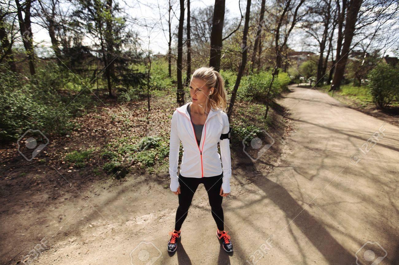 Banque d images - Jeune femme en vêtements d exercice debout sur un sentier  de la forêt à la recherche. Remise en forme féminine des sessions de  formation à ... 0b4eda5ac10