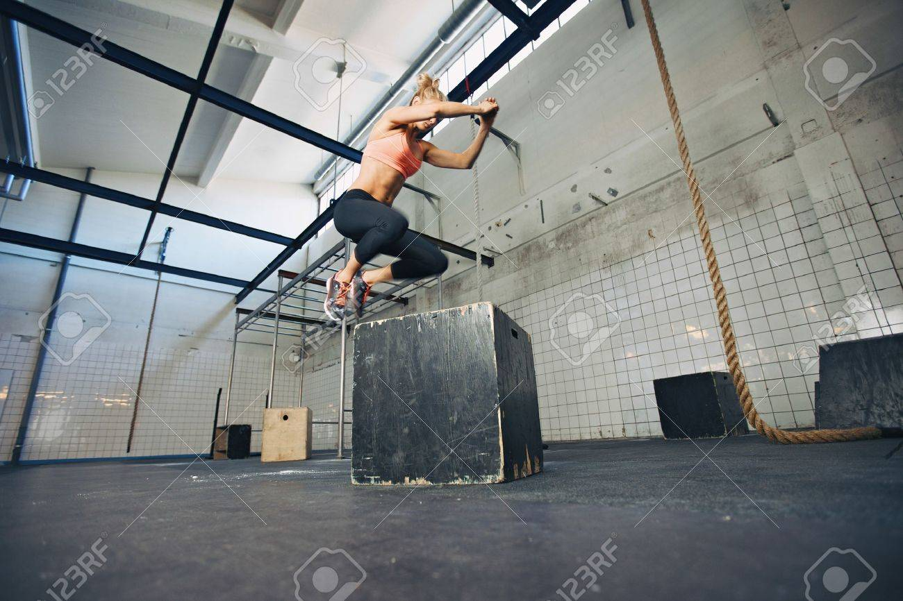 Low angle view of young female athlete box jumping at a crossfit gym. Fit woman is performing box jumps at gym. - 29385698