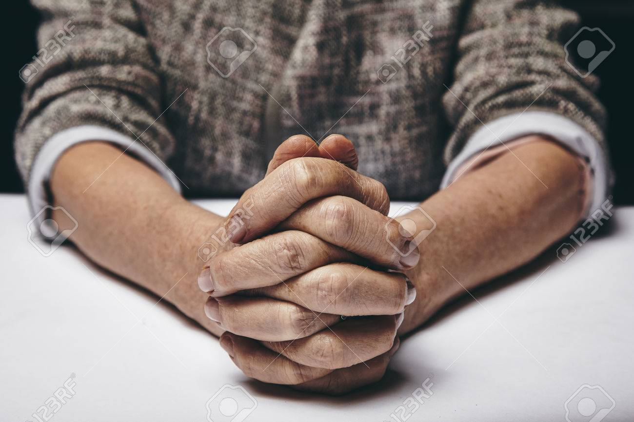 Studio Photography Of Praying Hands Of A Senior Woman On Table