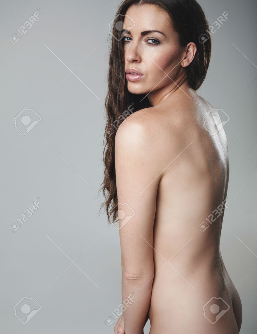 young nude model Sexy young brunette posing naked. Nude female model on grey background.  Stock Photo -