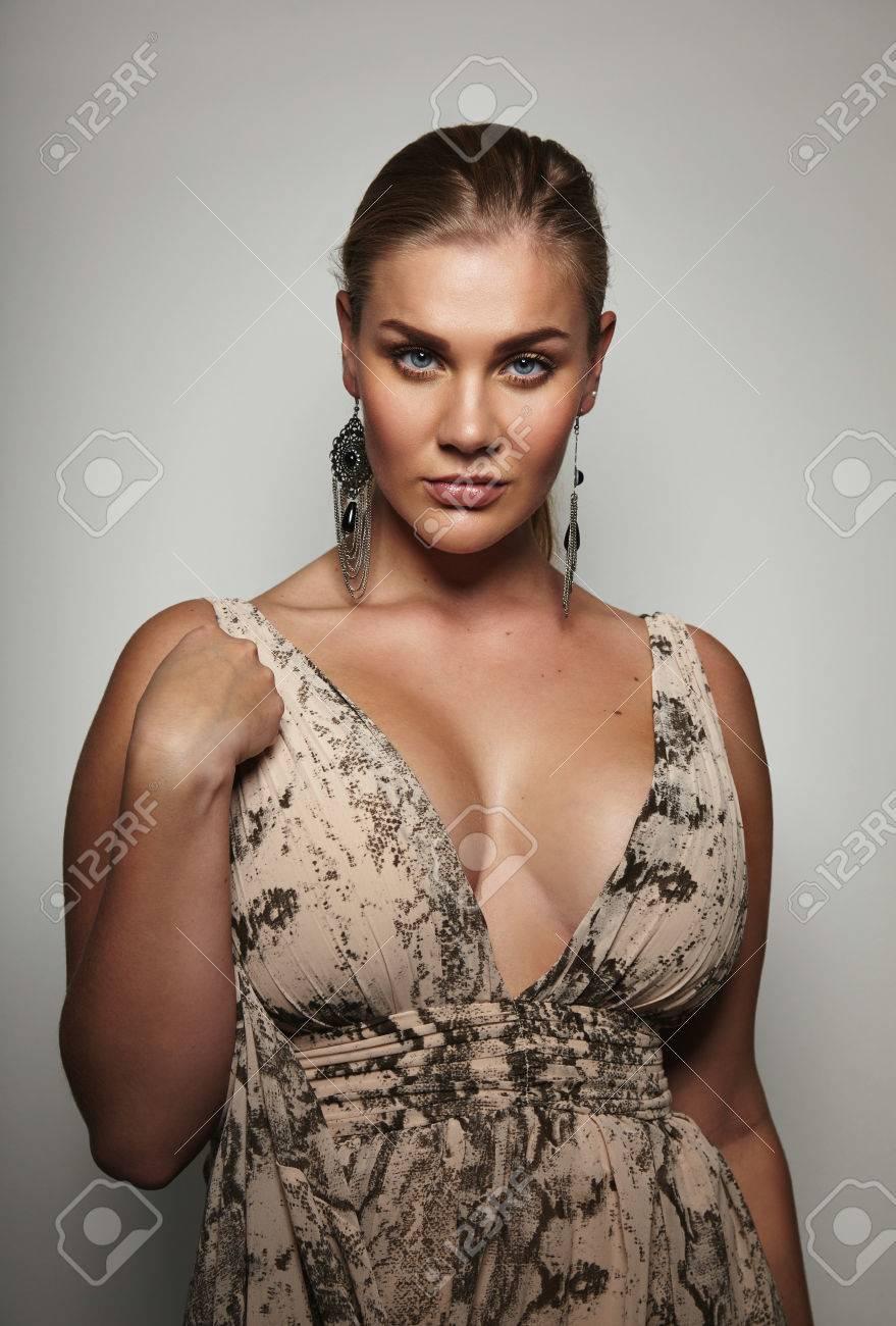 e025b9bce97 ... on grey background. Portrait of sensual female model in formal dress  posing to camera. Beautiful plus size woman