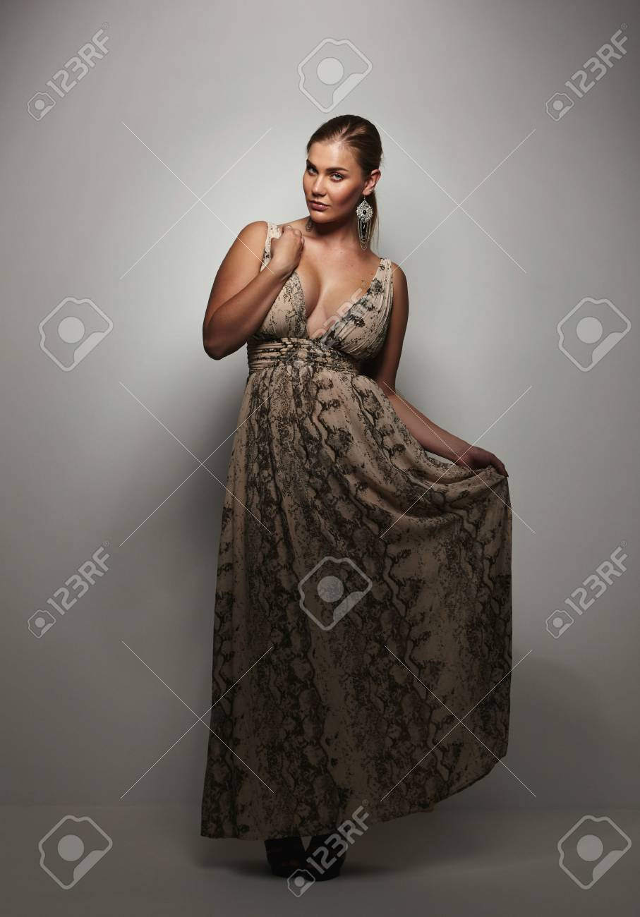 5f5bd6c6082 Beautiful young woman in a evening dress standing on grey background looking  at camera. Plus