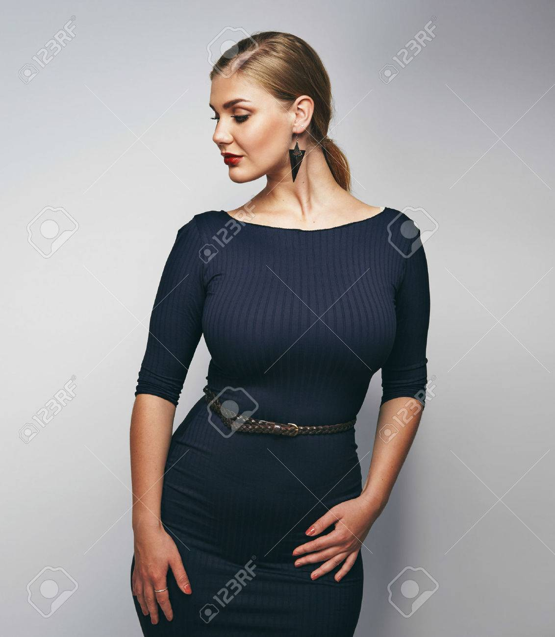 cdb6f9660c7 Portrait of confident female model posing against grey background. Plus size  young caucasian woman.