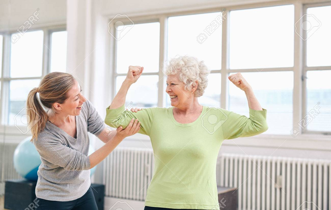 Portrait of female trainer looking at elderly woman flexing her bicep at the rehabilitation center. Happy about her recovery at rehab. - 34145803