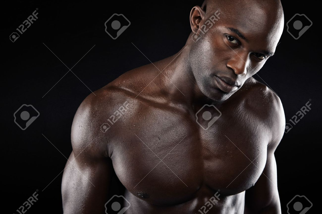 Close up image of young man with muscular build shirtless african male model with