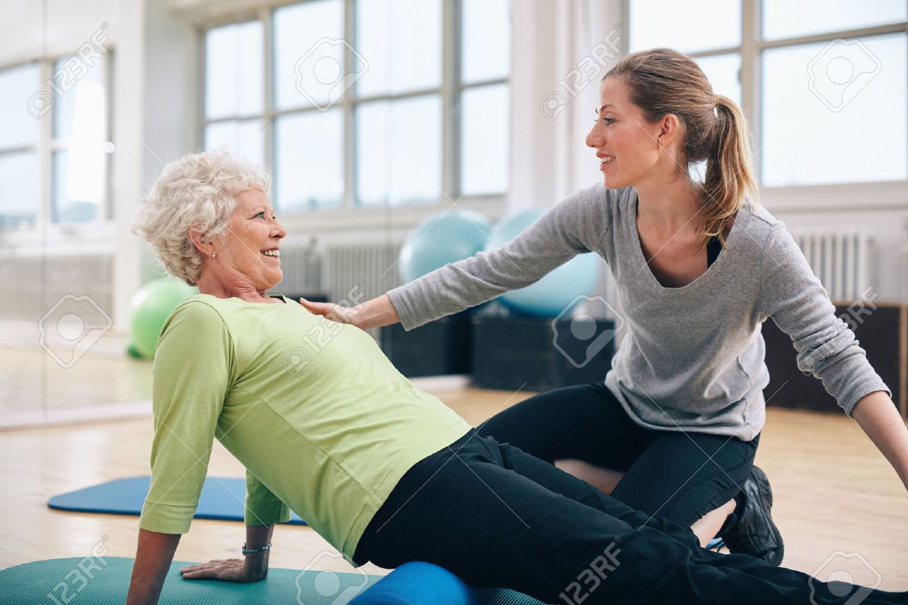 Physical therapist working with a senior woman at rehab. Female trainer helping senior woman doing exercise on foam roller at gym. - 35084418