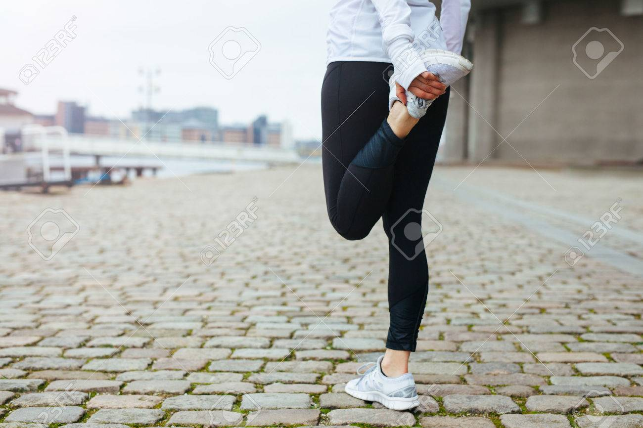 Low section view of fit young woman stretching her leg before a run in city streets. Preparation for running workout. - 35751743