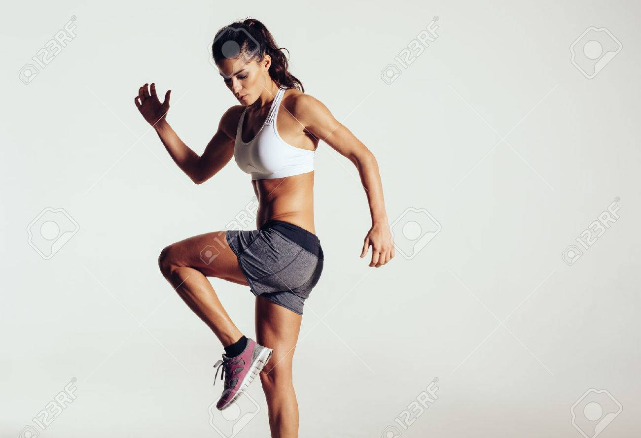 bd5e0a33e7 Attractive fit woman exercising in studio with copyspace. Image of healthy young  female athlete doing